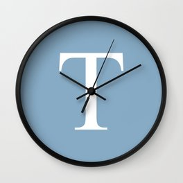 Letter T sign on placid blue background Wall Clock