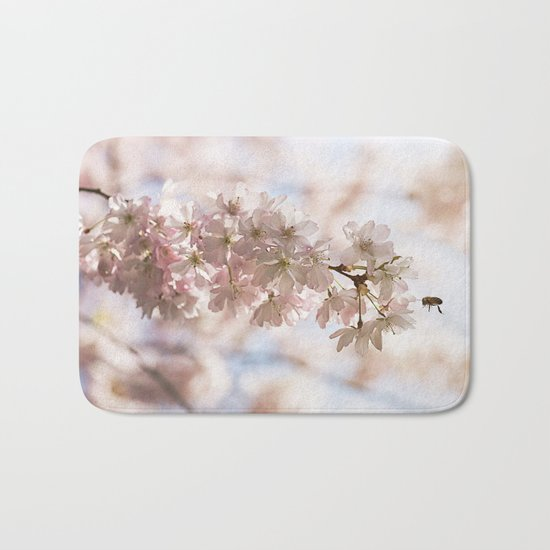 Bee and cherry branches against the blue sky Bath Mat