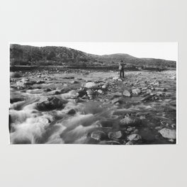 Man with rifle stands in mountain stream as it floods, east of Palmdale, California, ca.1920 Rug