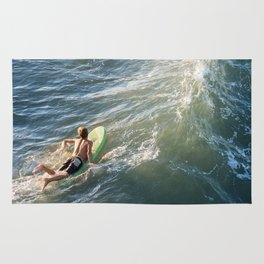 Surfer paddles out on surfboard without a wetsuit Rug