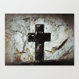 Wrought iron cross against stone Canvas Print