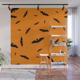 Flying black bats on an orange background in Halloween style Wall Mural