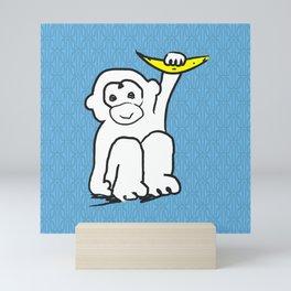 white monkey holding a banana Mini Art Print