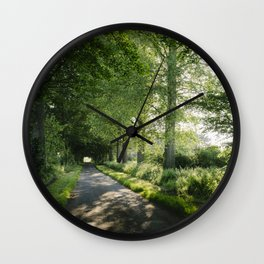 Sunlight through a remote country road lined with trees. Norfolk, UK. Wall Clock