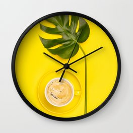 cup of coffee and tropical plant on yellow background Wall Clock