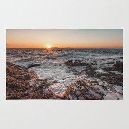 Sunset from rocky beach Rug