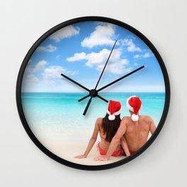 Christmas beach vacation couple relaxing in santa hats on Caribbean holidays Wall Clock