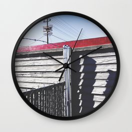 steel fence and wooden fence with red building in the city Wall Clock