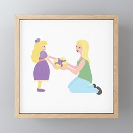 Daughter child gives a gift to Mother. Blonde girl present Framed Mini Art Print