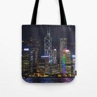 hong kong Tote Bags featuring Hong Kong Night Skyline by Deborah Janke