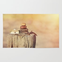Balanced stone cairn in sunset light Rug