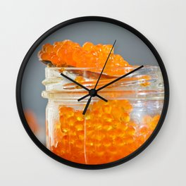 Macro shot of red caviar on jar on a gray background Wall Clock