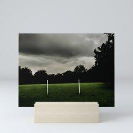 Football goalposts in an empty field Mini Art Print
