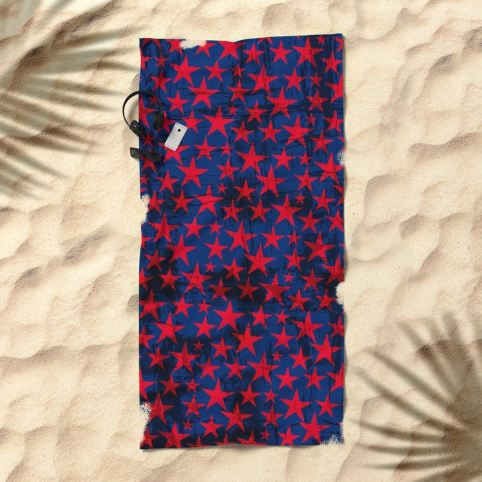 Red stars on grunge textured blue background Beach Towel