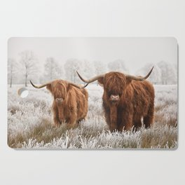 Hairy Scottish highlanders in a natural winter landscape. Cutting Board