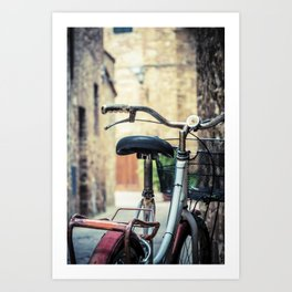 Red old bicycle in a little alley of a medieval village Art Print