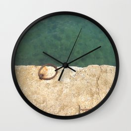 Teal waters and a rusty ring in a dock Wall Clock