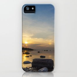 Sun with faint halo over the calm sea and reef rocks iPhone Case