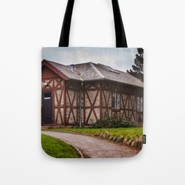 the cottage, a small house on the hill surrounded by greenery Tote Bag