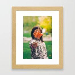 Girl holding a dry leaf Framed Art Print