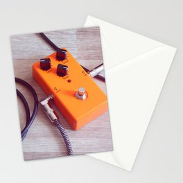 orange pedal effect and black cables on wooden floor. toning Stationery Cards