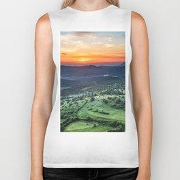 Beautiful sunset behind green fields Biker Tank