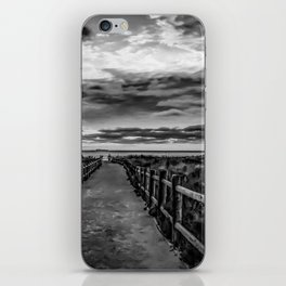 Walkway to the ocean with cloudy sky iPhone Skin