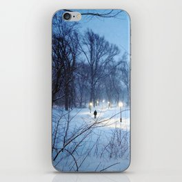 A man walking on a lit path through the snow in Central Park iPhone Skin