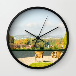 A couple of chairs on the top of a lookout watching the landscape I Wall Clock