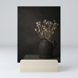 Moody still life of a vase with dried poppies Mini Art Print