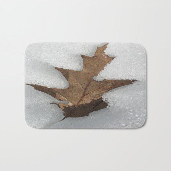 leaf in snow Bath Mat
