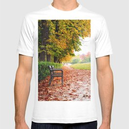 Park bench surrounded by fallen leaves during Autumn T-shirt