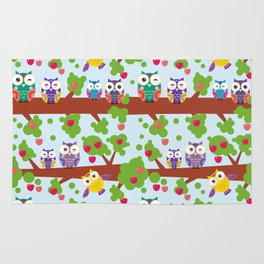 bright colorful owls on the branch of a tree with red apples on blue background Rug