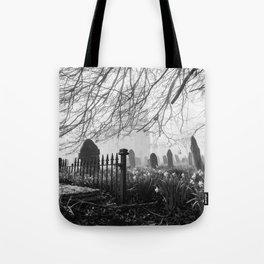 Rural church and graveyard in early morning fog. Hilborough, Norfolk, UK. Tote Bag