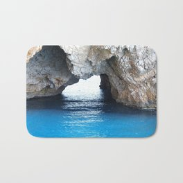 Rocks created a natural arch over crystal blue water Bath Mat