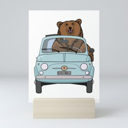 A smiling bear driving a small light blue car Mini Art Print