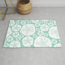 Teal and white sand dollars on the sea shore Rug