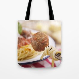 Spaghetti and meatball on a fork, plate in the background Tote Bag