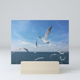 Seagulls or birds flying above the ocean in a clear blue sky Mini Art Print