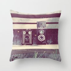 two cameras sitting on a park bench ...  Throw Pillow
