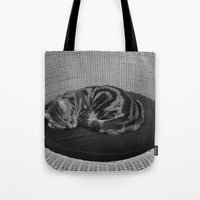 sofa Tote Bags featuring sleeping cat on sofa by gzm_guvenc