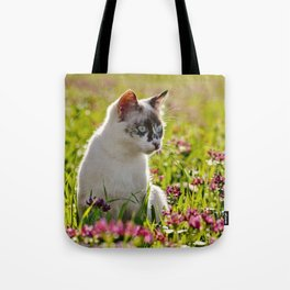 tortoiseshell cat in a meadow Tote Bag