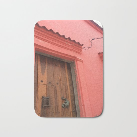 Cartagena is Peachy, Colombia, South America. Coral Pink Building with Ornate Lizard design Bath Mat