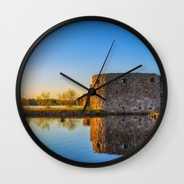 Ruins of old scandinavian castle or fort at sunset time at the lake Wall Clock