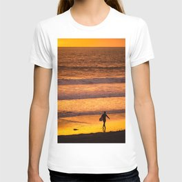 Surfer walking along beach at sunset T-shirt
