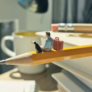 photo of miniatures of a man and dog sitting on a pencil