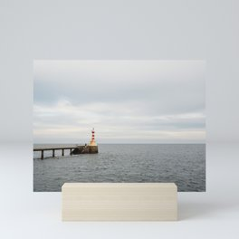 A small northumberland lighthouse stretched our to sea at dusk. Mini Art Print