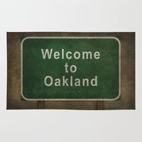 oakland Area & Throw Rugs featuring Welcome to Oakland road sign illustration by BruceStanfieldArtist.DarkSide