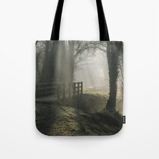 Sunlight through mist and fog over an old wooden footbridge. Norfolk, UK. Tote Bag