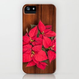 Red Christmas flower on brown wood iPhone Case